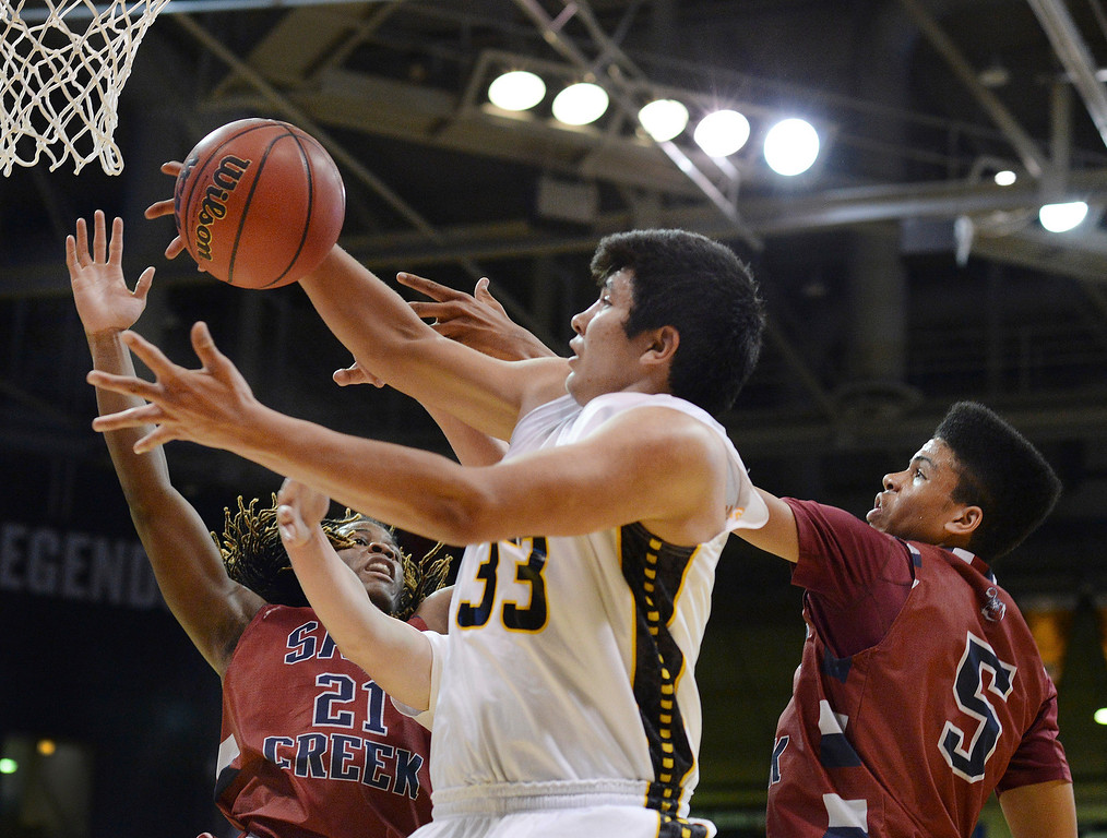 . BOULDER, CO - MARCH 14: Pueblo East center Jimmy Valdez (33) battled for a rebound with Sand Creek defenders Langston Bell (21) and Jason Pasley (5) in the first half. The Pueblo East High School boy\'s basketball team took on Sand Creek in a 4A semifinal game Friday night, March 14, 2014 in Boulder, Colorado. (Photo by Karl Gehring/The Denver Post)