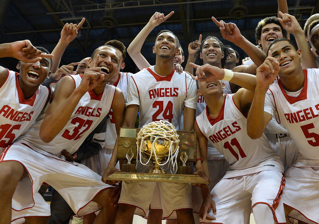 . BOULDER, CO - MARCH15: Dominique Collier held the trophy as the Angels celebrated the state 5A title Saturday night. The Denver East High School boy\'s basketball team took the 5A championship game with a 70-49 win over Fossil Ridge Saturday night, March 15, 2014 in Boulder, Colorado. (Photo by Karl Gehring/The Denver Post)