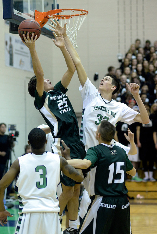 . Mountain Vista forward Graham Smith (25) encountered ThunderRidge center Zach Pirog (33) under the basket in the second half. The Mountain Vista High School boy\'s basketball team defeated ThunderRidge 60-50 Friday night, February 7, 2014. Photo By Karl Gehring/The Denver Post