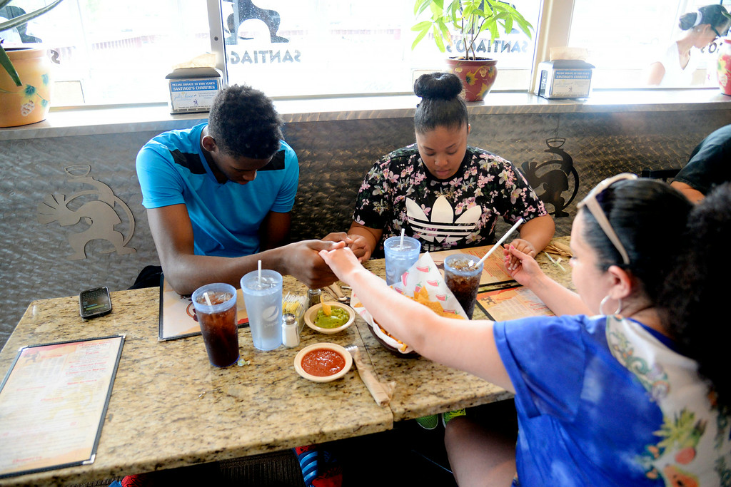 ". AURORA, CO - JULY 29: De\'Ron Davis prays with his girlfriend, Andrea Kelly (upper right) and her mother, Veronica Valencia, as they prepare to eat upon all returning from Las Vegas where De\'Ron played in an AAU basketball tournament. When asked if he played well, Valencia said, ""As always ... but he never thinks he does if they don\'t win.\"" De\'Ron Davis was photographed on Wednesday, July 29, 2014. (Photo by AAron Ontiveroz/The Denver Post)"