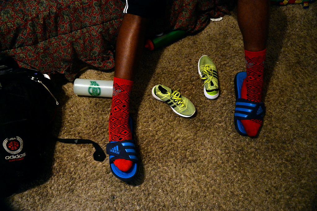 . AURORA, CO - JULY 29: De\'Ron Davis, who wears a size 17, sits on his bed with his girlfriend\'s size 4.5 sneakers between his feet. De\'Ron Davis was photographed on Wednesday, July 29, 2014. (Photo by AAron Ontiveroz/The Denver Post)