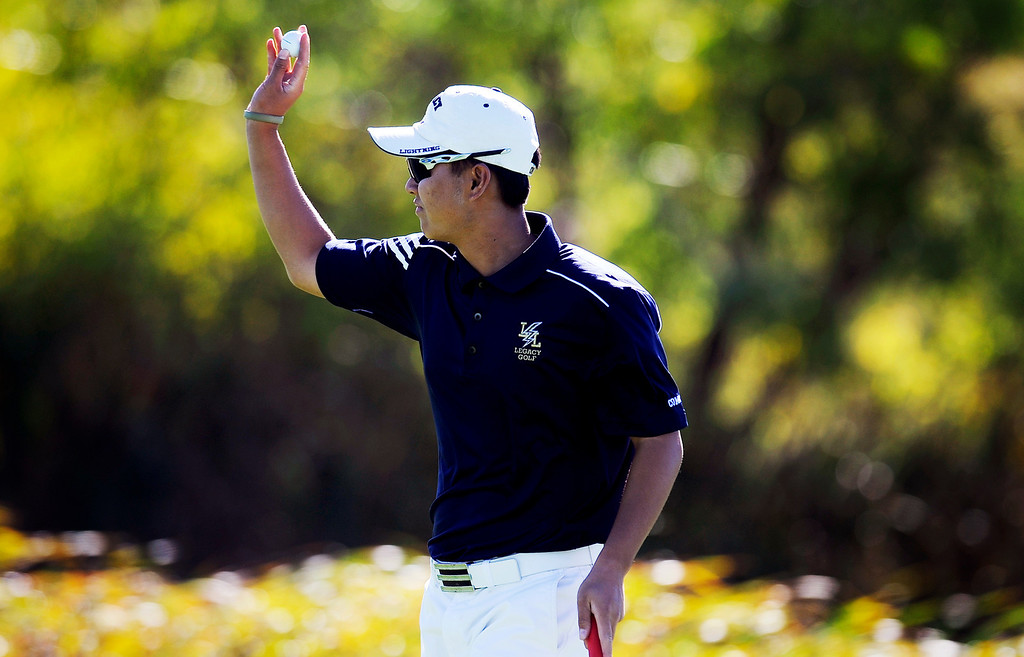 . Legacy\'s Li Chen waves to the crowd after knocking in his final shot at the 2013 Class 5A state golf finals. Chen tied for second in the tournament. (Photo By Erin Hull/The Denver Post)