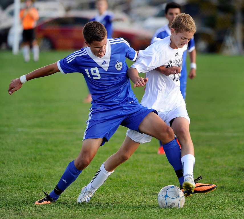 . Arapahoe defender Mitchell Fisher (13) tried to slow down Grandview striker Rhys De Sota (19) in the second half. The Grandview High School boy\'s soccer team defeated Arapahoe 2-0 Thursday evening, September 19, 2013.  Photo By Karl Gehring/The Denver Post