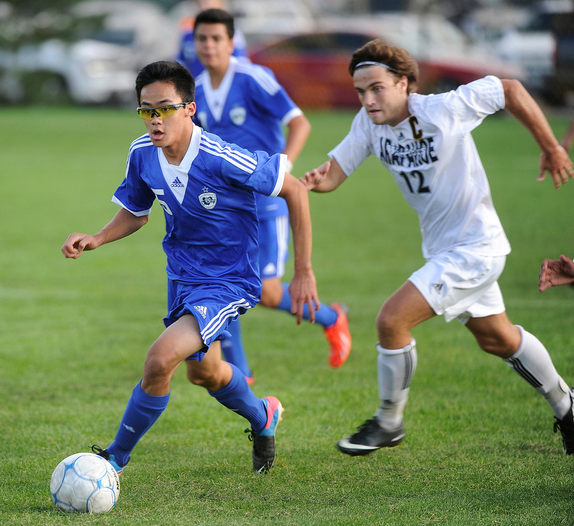 . LITTLETON, CO. - SEPTEMBER 19: Grandview midfielder Aaron Higa (15) raced past Arapahoe midfielder Noah Graham (12) in the second half. The Grandview High School boy\'s soccer team defeated Arapahoe 2-0 Thursday evening, September 19, 2013.  Photo By Karl Gehring/The Denver Post