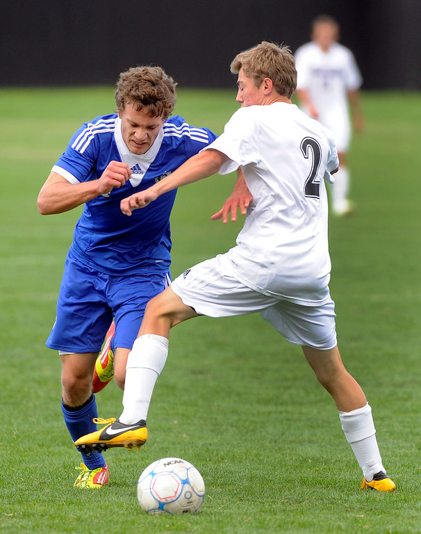 . Grandview midfielder Adam Riasati (4) made a move past Arapahoe midfielder Chase Brasher (2) in the first half. The Grandview High School boy\'s soccer team defeated Arapahoe 2-0 Thursday evening, September 19, 2013.  Photo By Karl Gehring/The Denver Post