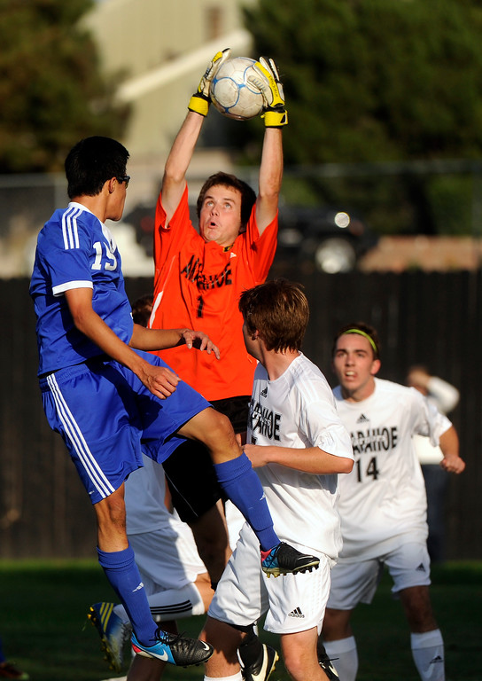 . Warriors\' goalkeeper Dan Scott (1) went up to make a save on a corner kick in the first half. The Grandview High School boy\'s soccer team defeated Arapahoe 2-0 Thursday evening, September 19, 2013.  Photo By Karl Gehring/The Denver Post