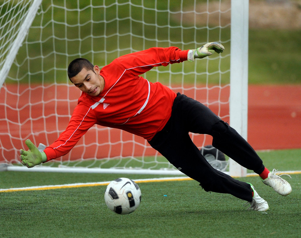 . AURORA, CO. - OCTOBER 15: Thunderbirds goalie Cruz Lopez Hernandez lunged at a shot in the first half.  The Rangeview High School boy\'s soccer team remained undefeated this season with a 3-0 win over Hinkley Tuesday evening, October 15, 2013. Photo By Karl Gehring/The Denver Post