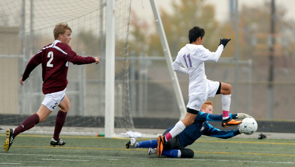. Golden\'s Jasper Hughes makes a save on a shot by North\'s Rodrigo de la Torre (11) during the first half.    (Photo by John Leyba/The Denver Post)