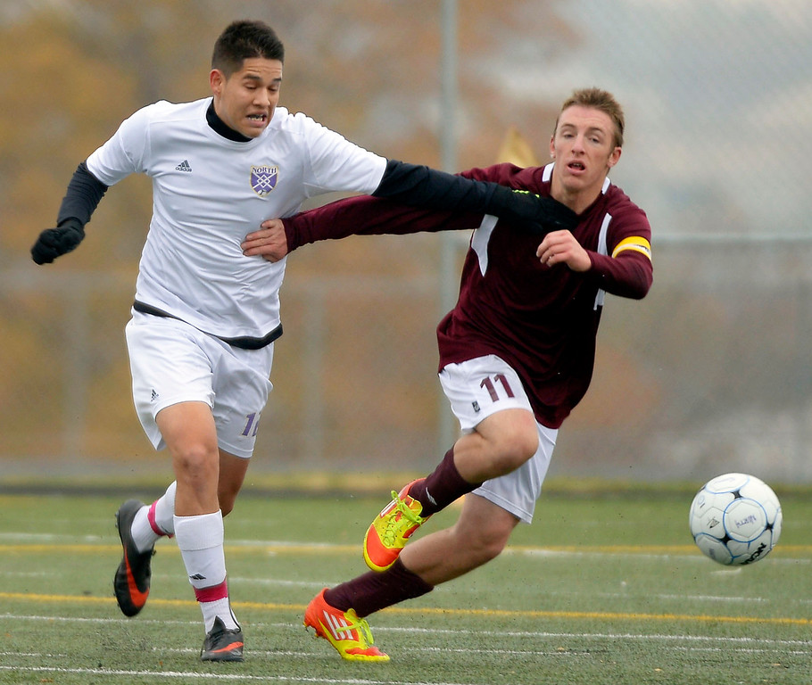 . North\'s Oscar Gozalez (12) and Golden\'s Phillip Katzman (11) race for the ball during the firs half.   (Photo by John Leyba/The Denver Post)