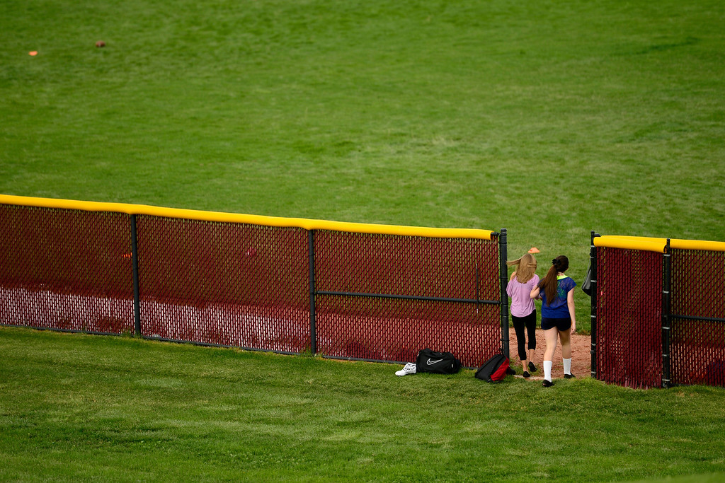 . Freshman managers Taylor Rose and Susan Mardoyan walk through a fence during the first day of practice. Cherokee Trail lost to Valor Christian in last year\'s 5A state title game. (Photo by AAron Ontiveroz/The Denver Post)