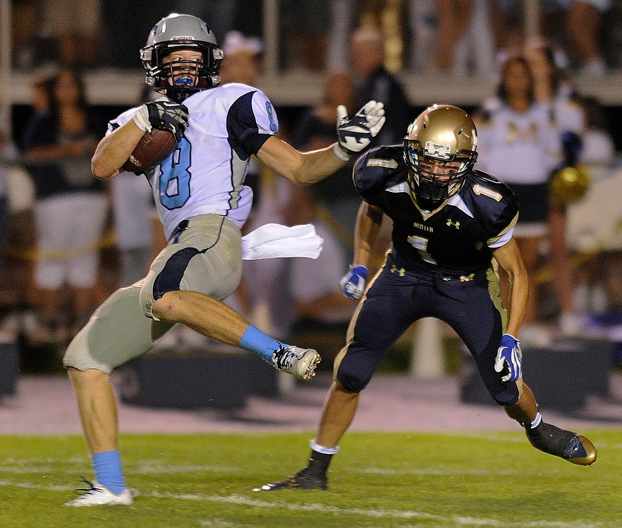 . DENVER, CO. - AUGUST 23: Ralston Valley receiver Kevin Meadows (8) twisted away from Mullen defensive back Robbie Smith (1) to score a touchdown in the third quarter. The Ralston Valley High School football team beat Mullen 43-0 Friday night, August 23, 2013. Photo By Karl Gehring/The Denver Post
