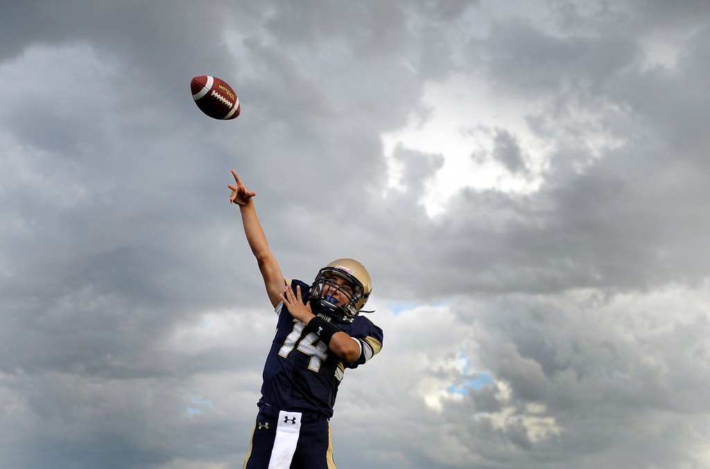 . DENVER, CO. - AUGUST 23: Mullen freshman quarterback Jovan Tafoya stretched out his arm under threatening skies before the game. The Mullen High School football team hosted Ralston Valley Friday night, August 23, 2013. Photo By Karl Gehring/The Denver Post
