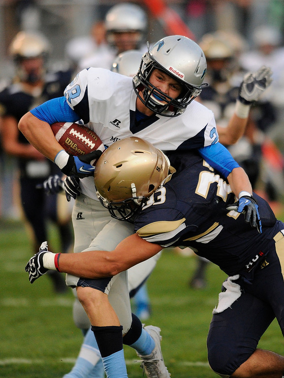 . DENVER, CO. - AUGUST 23: Ralston Valley junior Andrew Wingard (28) fought for a touchdown as Mullen junior Landon Urban (33) tried to make the tackle on a first quarter punt return Friday night. The Mullen High School football team hosted Ralston Valley Friday night, August 23, 2013. Photo By Karl Gehring/The Denver Post