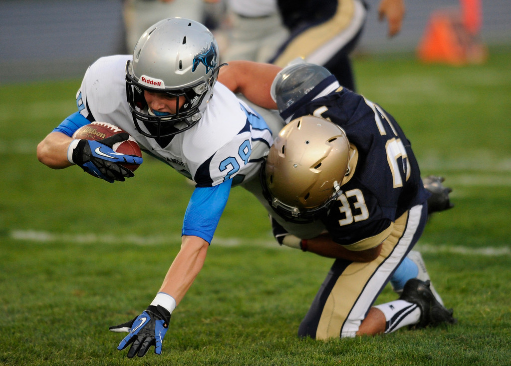 . DENVER, CO. - AUGUST 23: Ralton Valley junior Andrew Wingard (28) stretched for a touchdown as Mullen junior Landon Urban (33) tried to make the tackle on a first quarter punt return Friday night. The Mullen High School football team hosted Ralston Valley Friday night, August 23, 2013. Photo By Karl Gehring/The Denver Post