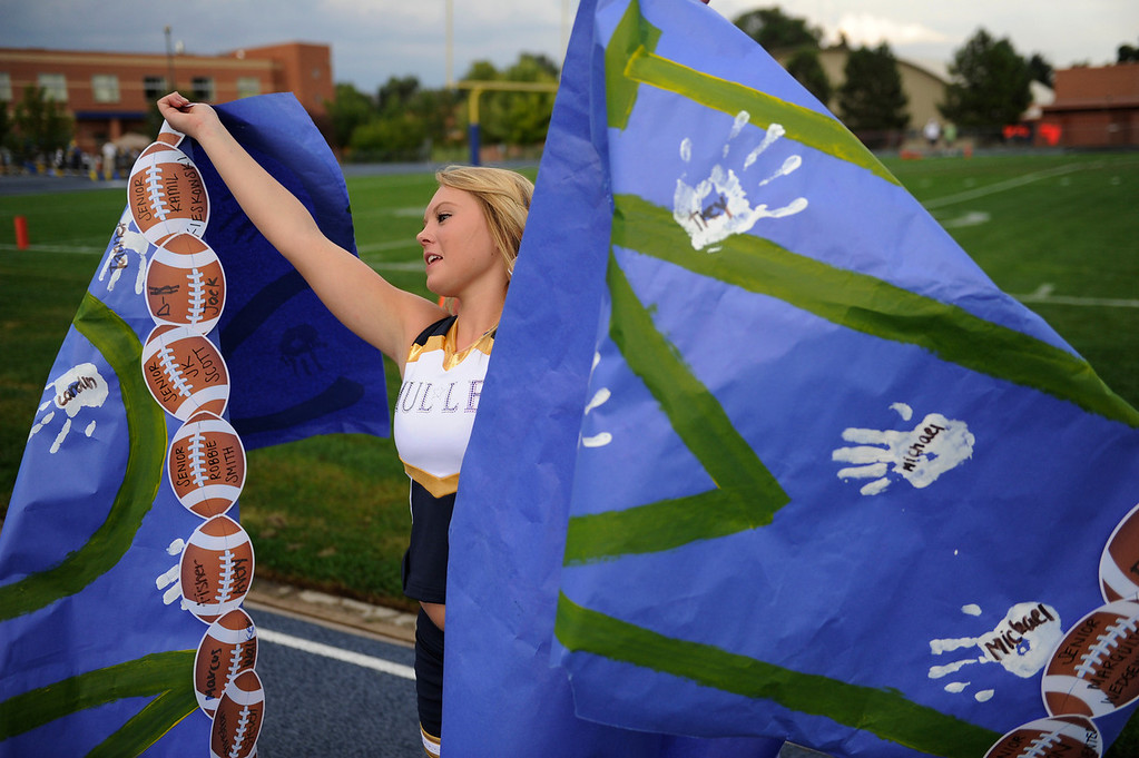 . DENVER, CO. - AUGUST 23: Mustangs Varsity cheerleader Briana Ridley held a banner off the wet ground before the game Friday. The Mullen High School football team hosted Ralston Valley Friday night, August 23, 2013. Photo By Karl Gehring/The Denver Post