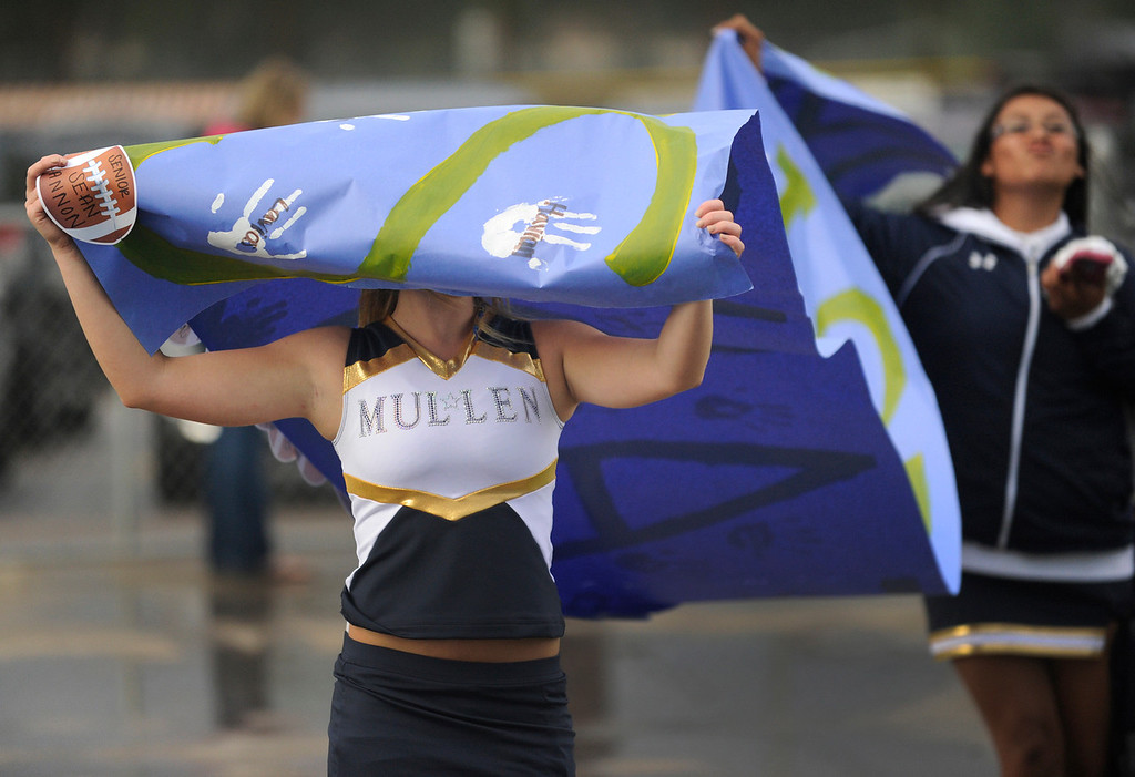 . DENVER, CO. - AUGUST 23: Mullen cheerleaders Briana Ridley, left, and Jazlynn Mitchell, right, carried a banner through the rain before the game Friday. The Mullen High School football team hosted Ralston Valley Friday night, August 23, 2013. Photo By Karl Gehring/The Denver Post