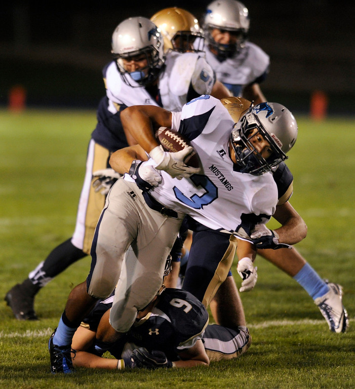 . DENVER, CO. - AUGUST 23: Ralston Valley running back John Morales (3) was dragged down by Mullen defender Trey Taylor in the third quarter. The Ralston Valley High School football team beat Mullen 43-0 Friday night, August 23, 2013. Photo By Karl Gehring/The Denver Post