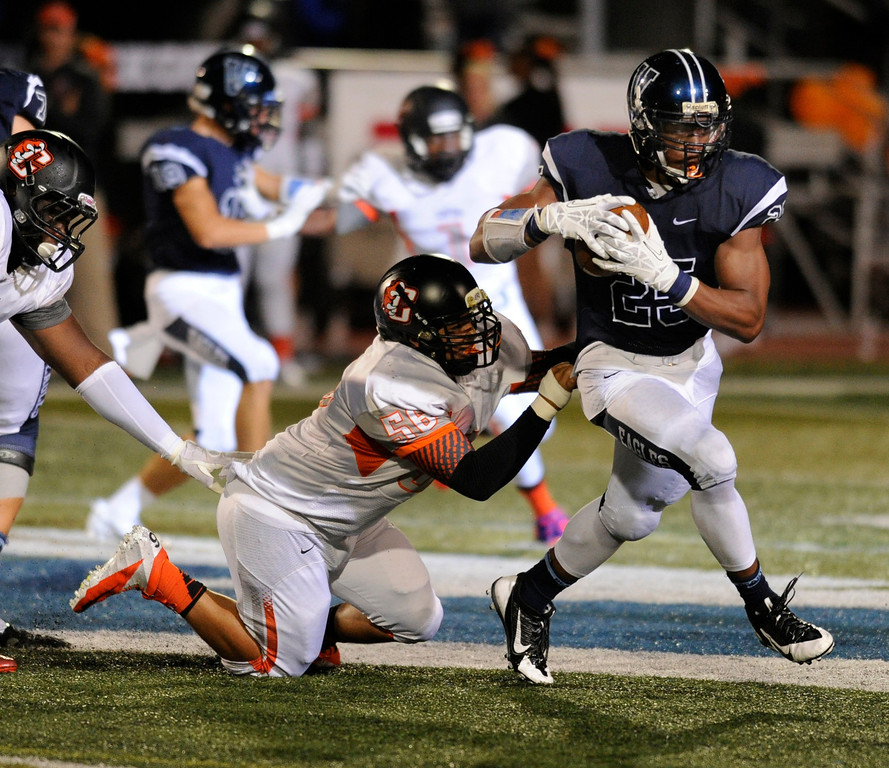 . DENVER, CO. - AUGUST 24: Grizzlies defensive lineman Jonathan Williams (56) tried to bring down Valor fullback Gabriel Watkins (25) in the third quarter. The Valor Christian High School football team hosted Central East Saturday night, August 24, 2013 in a nationally televised game. Photo By Karl Gehring/The Denver Post