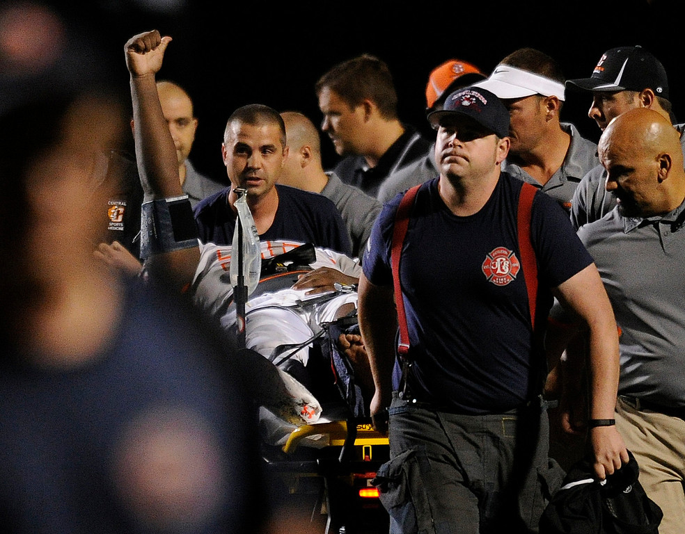 . DENVER, CO. - AUGUST 24: Grizzlies\' lineman Sharif Williams acknowledged the crowd as Littleton paramedics carted him off the field. It looked like Williams broke a bone in his leg on a play in the second quarter. The Valor Christian High School football team hosted Central East Saturday night, August 24, 2013 in a nationally televised game. Photo By Karl Gehring/The Denver Post