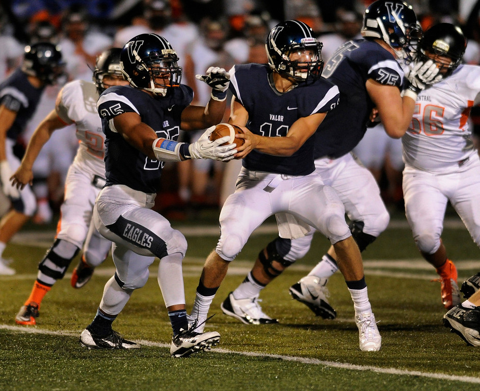 . DENVER, CO. - AUGUST 24: Eagles quarterback A.J. Cecil made the hand-off to running back Gabriel Watkins in the third quarter. The Valor Christian High School football team hosted Central East Saturday night, August 24, 2013 in a nationally televised game. Photo By Karl Gehring/The Denver Post