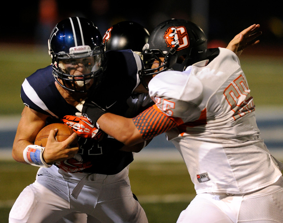 . DENVER, CO. - AUGUST 24: Grizzlies lineman Ernesto Gutierrez (65) tried to bring down Valor quarterback A.J.Cecil (11) in the third quarter. The Valor Christian High School football team hosted Central East Saturday night, August 24, 2013 in a nationally televised game. Photo By Karl Gehring/The Denver Post