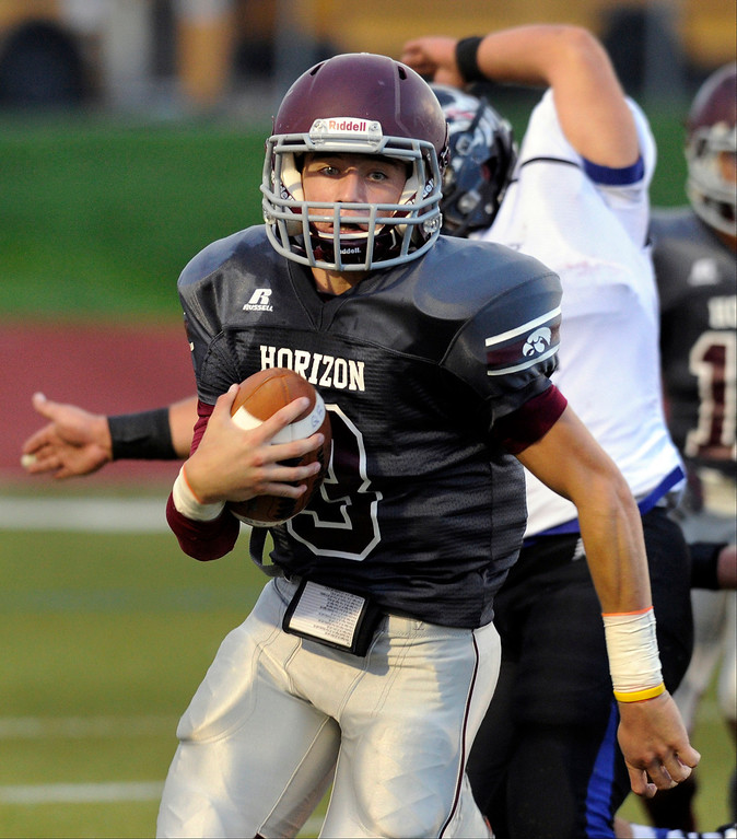 . Hawks quarterback Ayden Karracker (3) scrambled out of the pocket in the first quarter. The Horizon High School football team hosted Grandview Thursday night, August 29, 2013.  Photo By Karl Gehring/The Denver Post