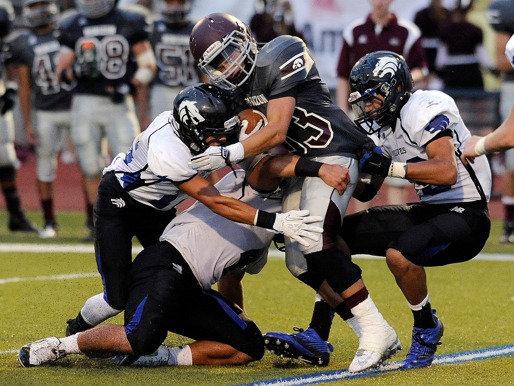 . Hawks running back Bryce Killmon (33) was swarmed by Grandview defenders on a rush up the middle in the first half. The Horizon High School football team hosted Grandview Thursday night, August 29, 2013.  Photo By Karl Gehring/The Denver Post