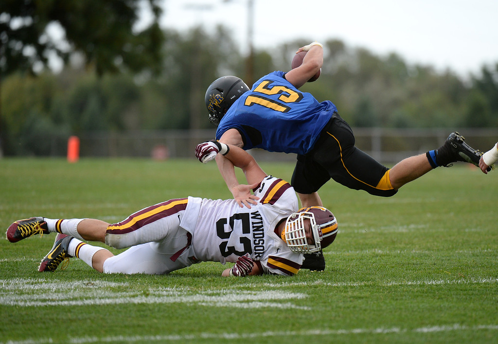 . LAKEWOOD, CO - August 30 : QB Tanner Weakland of Wheat Ridge High School (15) escapes from the pressure of Zach Peck of Windsor High School (53) in the first half of the game at Jefferson County Stadium. Lakewood, Colorado. August 30, 2013. (Photo by Hyoung Chang/The Denver Post)
