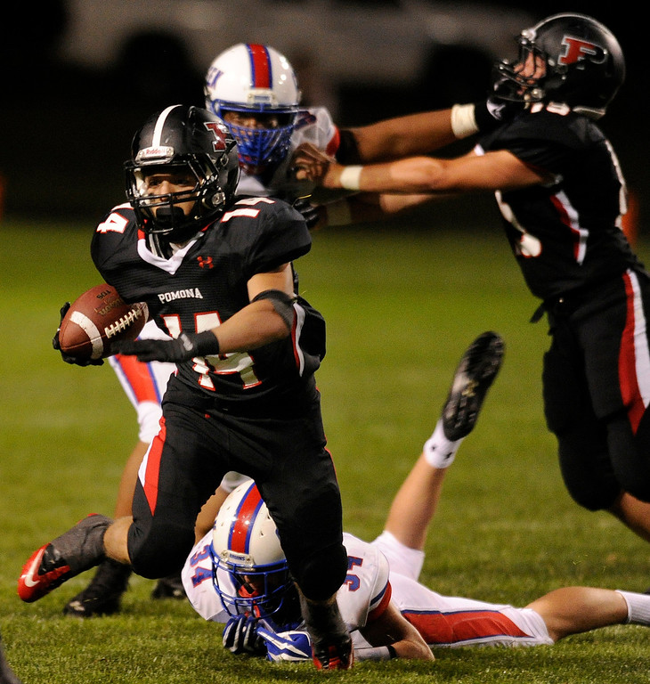 . ARVADA, CO. - SEPTEMBER 6: Panthers\' running back Chris Marquez (14) got away from Creek\'s Mike Morean (34) in the third quarter. The Cherry Creek High School football team defeated Pomona 19-15 Friday night, September 6, 2013. Photo By Karl Gehring/The Denver Post