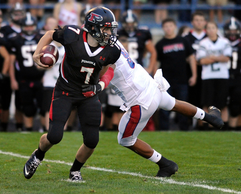 . ARVADA, CO. - SEPTEMBER 6: Panthers\' quarterback Justin Roberts (7) twisted away from Bruins\' defender Jaylon Jones in the first quarter. The Pomona High School football team hosted Cherry Creek Friday night, September 6, 2013. Photo By Karl Gehring/The Denver Post
