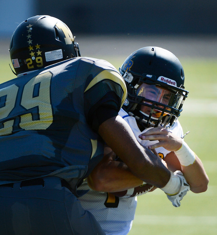 . LAFAYETTE, CO - SEPTEMBER 07: Monarch LB, Peter Mitchell, left, wraps up Wheat Ridge QB, Ryen Kahl, right, in the second quarter of play at the Howard Spangenberg Field in Lafayette Colorado, Saturday morning, September 07, 2013. (Photo By Andy Cross/The Denver Post)
