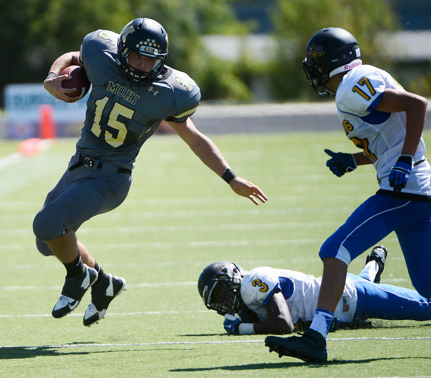 . LAFAYETTE, CO - SEPTEMBER 07: Monarch High RB, Braden Pape, left, escapes a loose tackle by Anthony McGinnis, second from left, Wheat Ridge and gets pursued by Dakota Koenecke, right,  in the third quarter of play at the Howard Spangenberg Field in Lafayette Colorado, Saturday morning, September 07, 2013. (Photo By Andy Cross/The Denver Post)