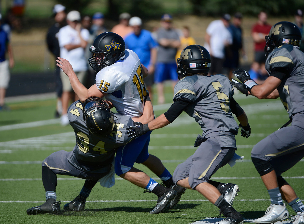 . LAFAYETTE, CO - SEPTEMBER 07: Wheat Ridge QB, Tanner Weakland, left, gets tackled by Kidd Sole, Monarch High, and pursued by Monarch players, Jaylen Alexander, third from left, and Philip Bubernak in the first quarter of play at the Howard Spangenberg Field in Lafayette Colorado, Saturday morning, September 07, 2013. (Photo By Andy Cross/The Denver Post)