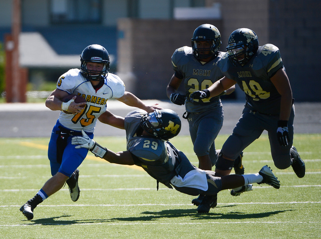 . LAFAYETTE, CO - SEPTEMBER 07: Wheat Ridge kick returner, Tanner Weakland, left, shrugs off Monarch defenders, Peter Mitchell, #29, Sam Lopez, #20, and Darien Sanders, right, in the second quarter of play at the Howard Spangenberg Field in Lafayette Colorado, Saturday morning, September 07, 2013. (Photo By Andy Cross/The Denver Post)