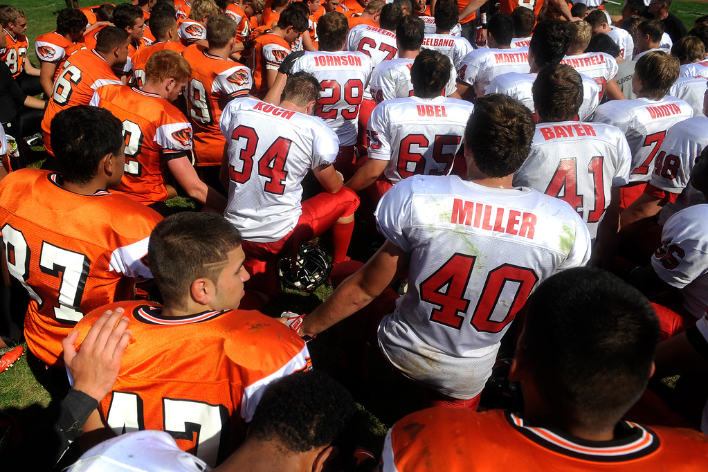 """. \""""Our Father, who art in heaven�,\"""" the players recite in unison as they gather together in the middle of the field after the game. Lakewood team leaders stood and voiced their prayers and support for the members of Fairview, who are in an area affected by the floods.  (Photo By Erin Hull/The Denver Post)"""