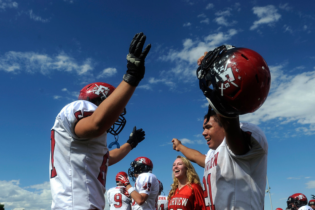 . Will Sheerin heads off the field and is greater with a celebratory hug by Jason Harvey. Fairview had just scored what ended up being the winning field goal.  (Photo By Erin Hull/The Denver Post)