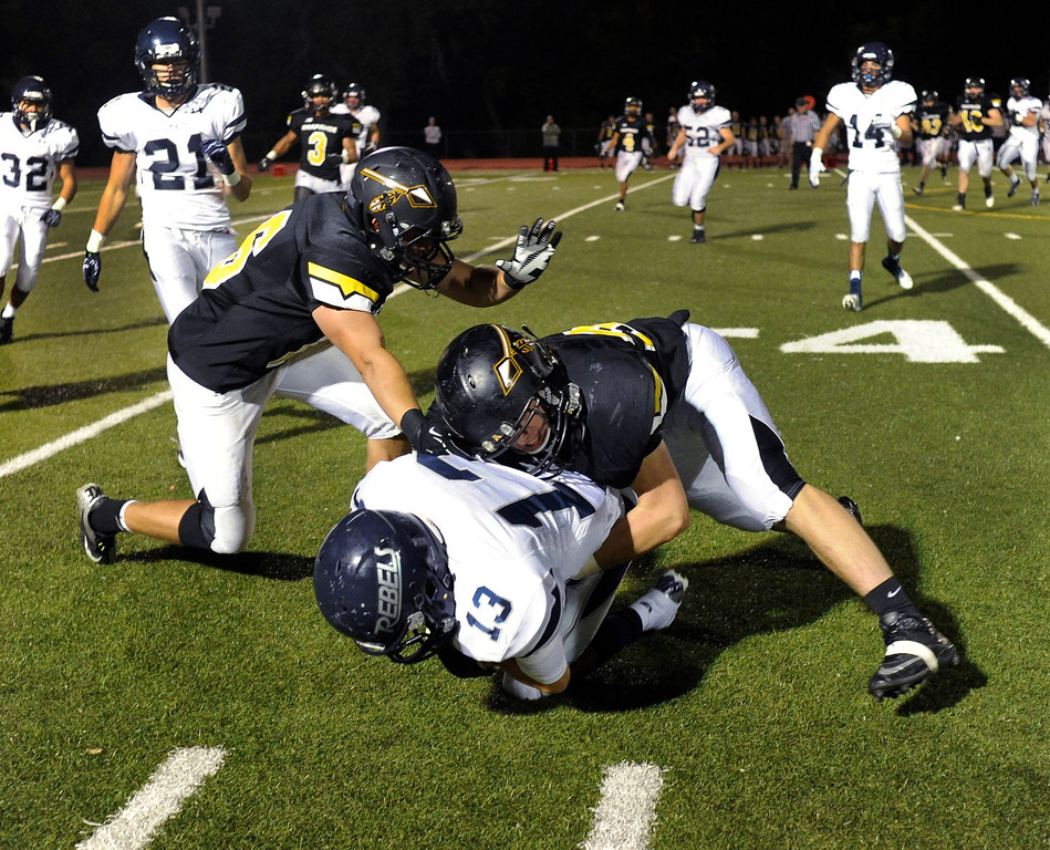 . Warriors linebacker Charlie Leonard (33) brought down Columbine quarterback Tyler Goodwin (13) in the fourth quarter. The Arapahoe High School football team defeated Columbine 49-28 at the Littleton Public Schools District Stadium Thursday night, September 26, 2013. Photo By Karl Gehring/The Denver Post