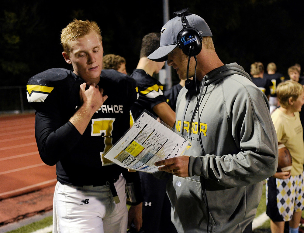 . Warriors assistant head coach talked with quarterback Gabe Peterson on the sidelines in the second half. The Arapahoe High School football team defeated Columbine 49-28 at the Littleton Public Schools District Stadium Thursday night, September 26, 2013. Photo By Karl Gehring/The Denver Post
