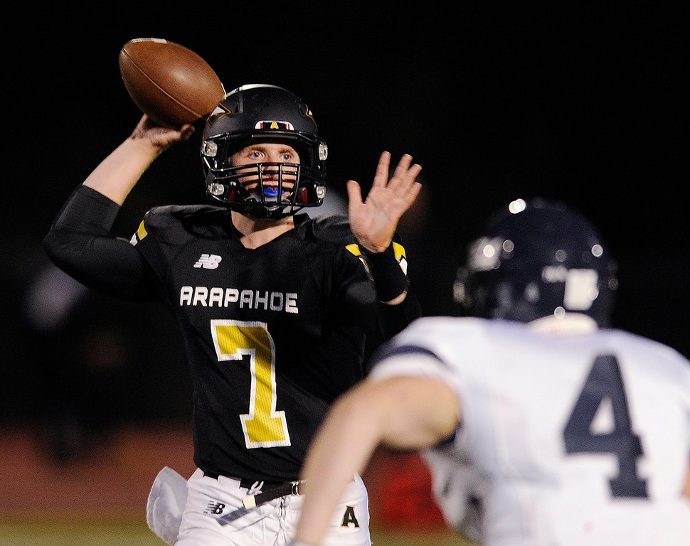 . Arapahoe quarterback Gabe Peterson (7) threw under pressure from Columbine linebacker Larry Munson (4) in the first quarter. The Arapahoe High School football team hosted Columbine at the Littleton Public Schools District Stadium Thursday night, September 26, 2013. Photo By Karl Gehring/The Denver Post