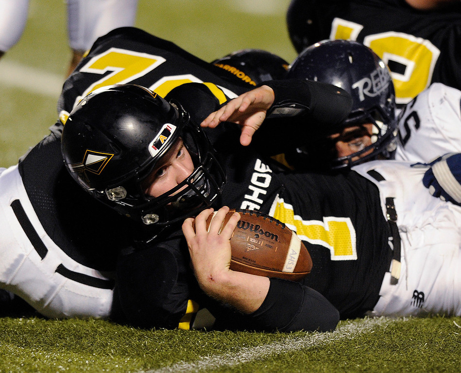 . Warriors quarterback Gabe Peterson (7) picked up the first down on a QB keeper in the fourth quarter. The Arapahoe High School football team defeated Columbine 49-28 at the Littleton Public Schools District Stadium Thursday night, September 26, 2013. Photo By Karl Gehring/The Denver Post
