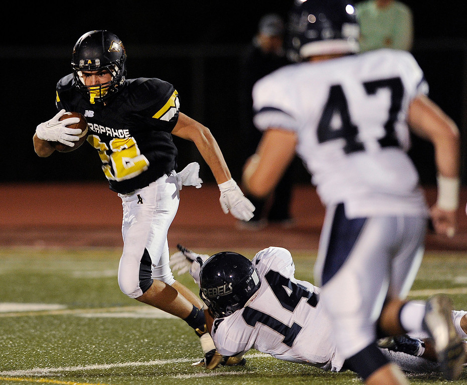 . Columbine defensive back Tanner Degutis (14) dived at the feet of Arapahoe running back Bryan Daldegan (22) in the first quarter. The Arapahoe High School football team hosted Columbine at the Littleton Public Schools District Stadium Thursday night, September 26, 2013. Photo By Karl Gehring/The Denver Post