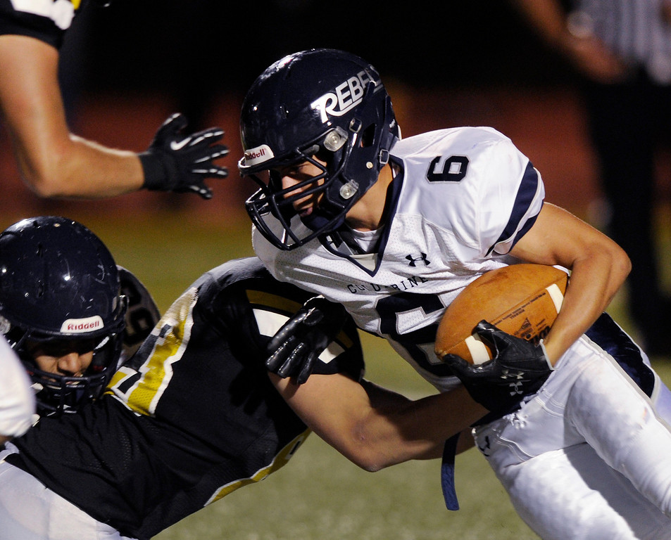 . Arapahoe defensive end Zachary Wikle (93) stopped Columbine running back Austin Norton (6) for a loss of four yards in the second quarter. The Arapahoe High School football team hosted Columbine at the Littleton Public Schools District Stadium Thursday night, September 26, 2013. Photo By Karl Gehring/The Denver Post