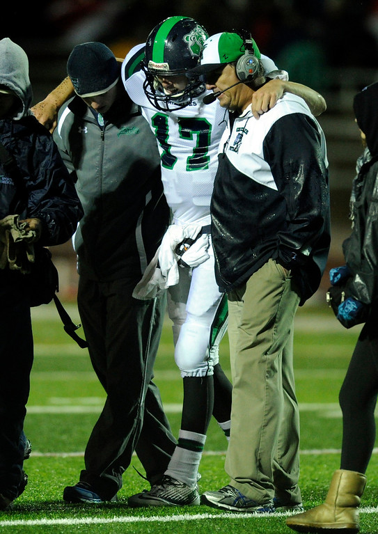 . AURORA, CO. - SEPTEMBER 27: Coaches helped ThunderRidge quarterback Brody Westmoreland from the field after he injured his knee in the second half. Westmoreland did not return to the game. The Regis Jesuit High School football team steamrolled  ThunderRidge 35-12 Friday night, September 27, 2013. Photo By Karl Gehring/The Denver Post