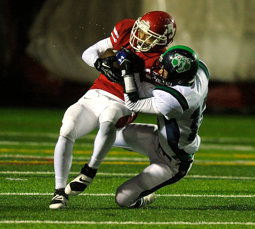 . AURORA, CO. - SEPTEMBER 27: Regis Jesuit wide receiver Trevor Williams (3) came down with a catch while ThunderRidge defensive back Austin Fafjer (16) brought him down in the first quarter. The Regis Jesuit High School football team hosted ThunderRidge Friday night, September 27, 2013. Photo By Karl Gehring/The Denver Post