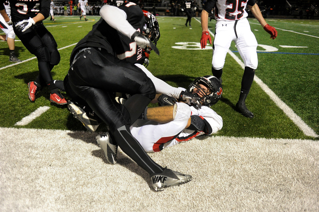 . BOULDER, CO. - NOVEMBER 15: Fairview defender Jonathan Swartzwelter (7) helped push Pomona running back Chris Benefiel (22) out of bounds in the first half. The Fairview High School football team defeated Pomona 35-24 Friday night, November 15, 2013. Photo By Karl Gehring/The Denver Post