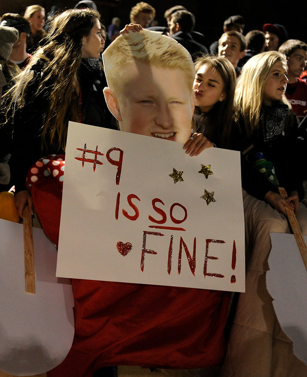 . BOULDER, CO. - NOVEMBER 15: Fairview student Natalie Sprowl playfully kissed a photo of her boyfriend Anders Hill.  Hill is the starting quarterback for the Knights. The Fairview High School football team defeated Pomona 35-24 Friday night, November 15, 2013. Photo By Karl Gehring/The Denver Post