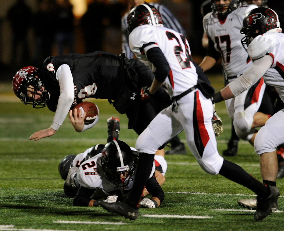 . BOULDER, CO. - NOVEMBER 15: Fairview quarterback Anders Hill (9) was knocked to the turf by Pomona defender Isaac Marquez (27) in the second half. The Fairview High School football team defeated Pomona 35-24 Friday night, November 15, 2013. Photo By Karl Gehring/The Denver Post