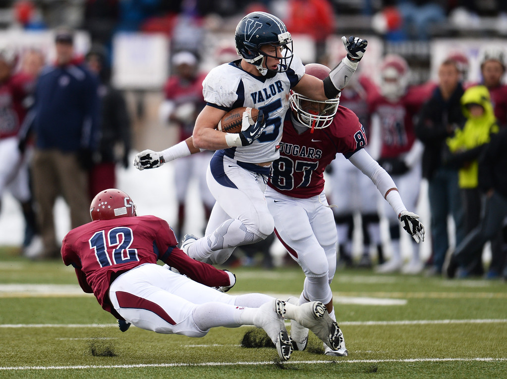 . AURORA CO. NOVEMBER 23 : Christian McCaffrey of Valor Christian High School (5) controls the ball against Thomas Thortvedt (12) and Ronnie Barfield (87) of Cherokee Trail High School during the 5A football semifinal game at Legacy Stadium in Aurora, Colorado November 23, 2013. Valor Christian won 42-23. (Photo by Hyoung Chang/The Denver Post)