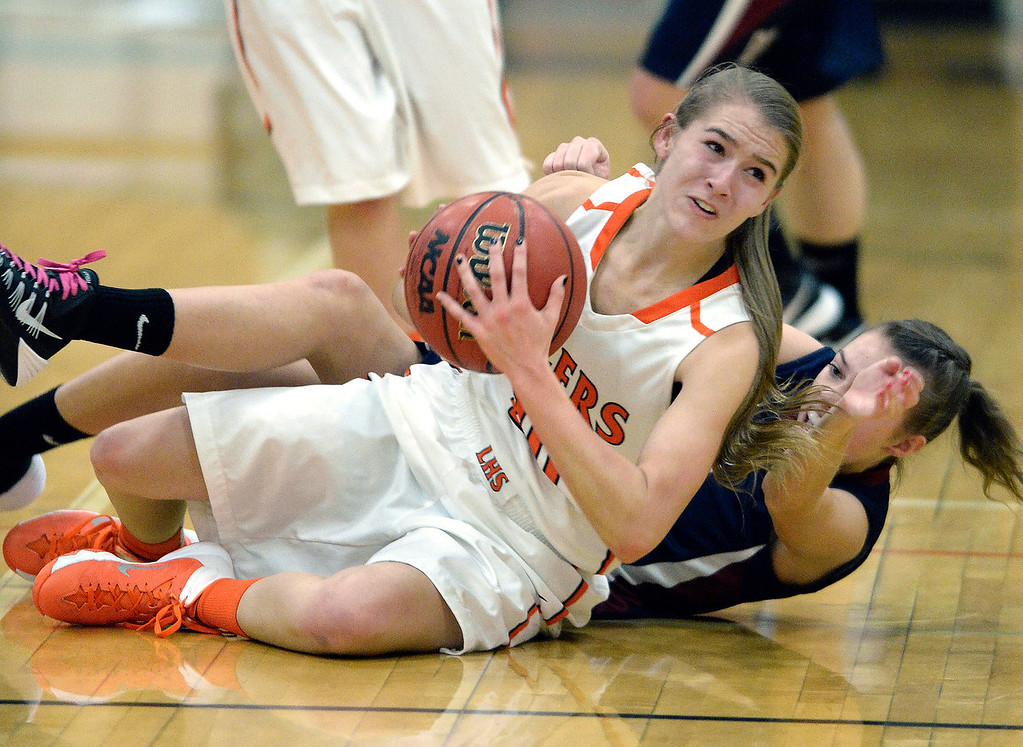 . Lakewood guard Madeline Miller (20) won the race to a loose ball with Dakota Ridge junior Aly Suniga (12) in the first half. The Lakewood High School girl\'s basketball team hosted Dakota Ridge Wednesday night, January 22, 2014. Photo By Karl Gehring/The Denver Post