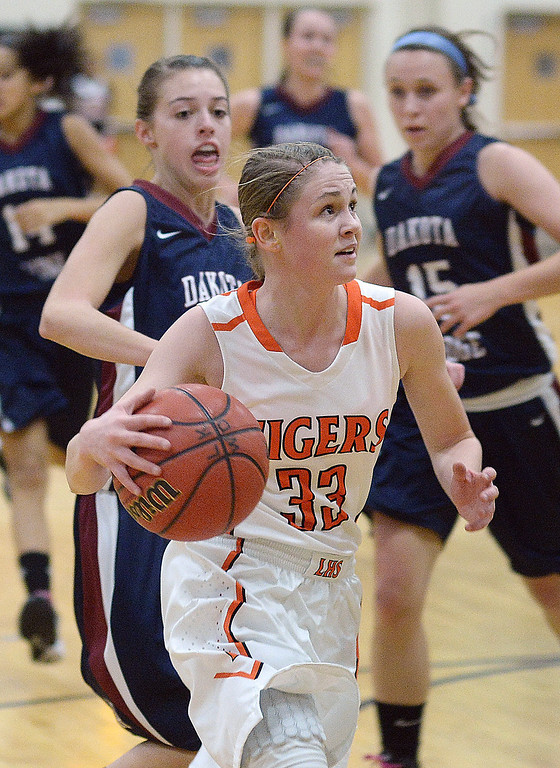 . Lakewood guard Mackenzie Forrest (33) drove past Dakota Ridge defenders in the first half.  Photo By Karl Gehring/The Denver Post